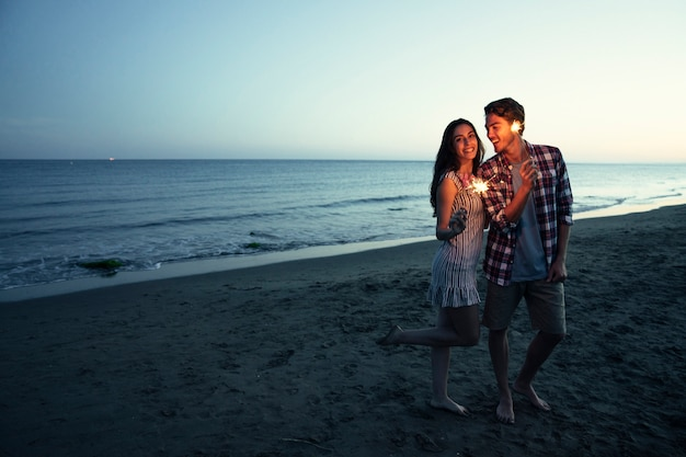 Romantic couple with sparkler at a sunset beach