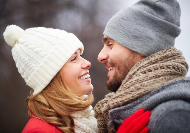 Coppie romantiche con cappelli di lana e guardando a vicenda