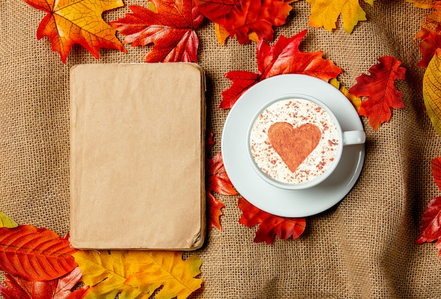 Romantic cup of coffee and book with autumn leaves on burlap background. top view