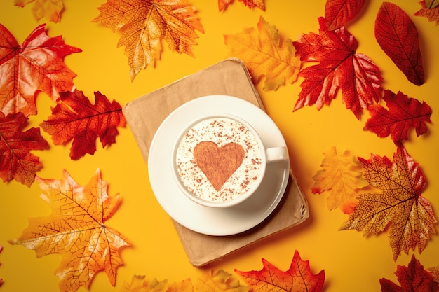 Romantic cup of coffee and book with autumn leaves on yellow background. top view