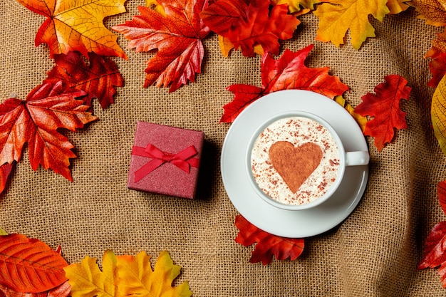 Romantic cup of coffee and gift box with autumn leaves on burlap background. top view