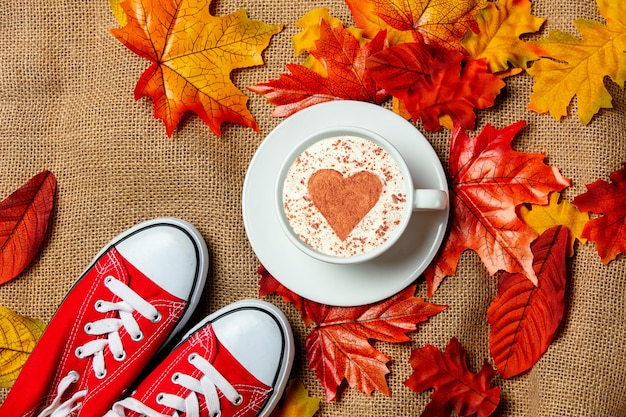 Romantic cup of coffee and gumshoes with autumn leaves on burlap background. top view
