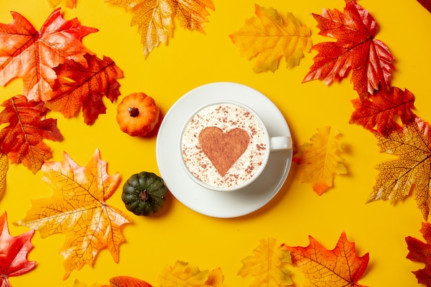 Romantic cup of coffee and little pumpkins with autumn leaves on yellow background. top view