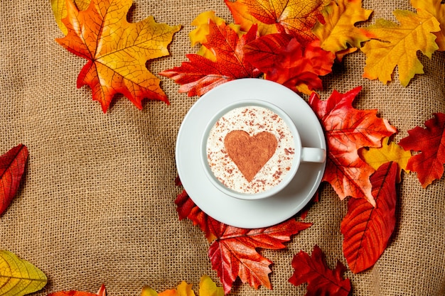 Romantic cup of coffee with autumn leaves on burlap background. top view