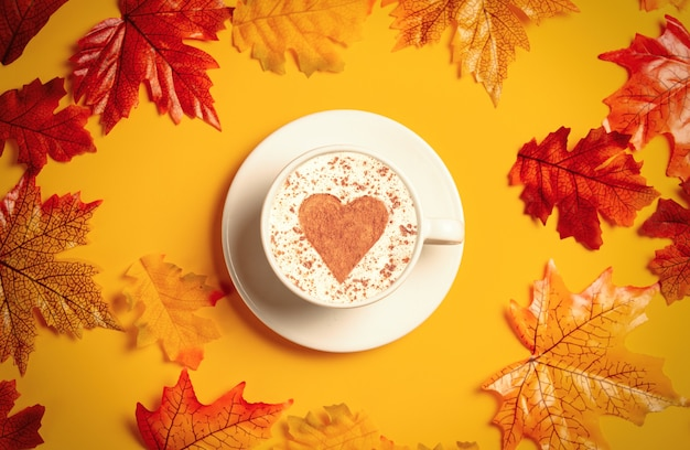 Romantic cup of coffee with autumn leaves on yellow background. top view