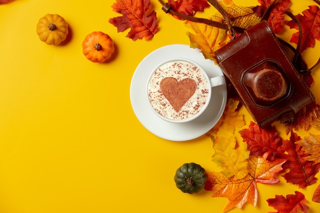 Romantic cup of coffee with vintage camera autumn leaves on yellow background. top view