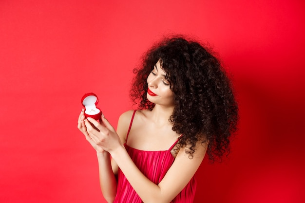 Romantic curly-haired woman in red dress, looking happy at engagement ring, become a bride, standing on studio background. copy space