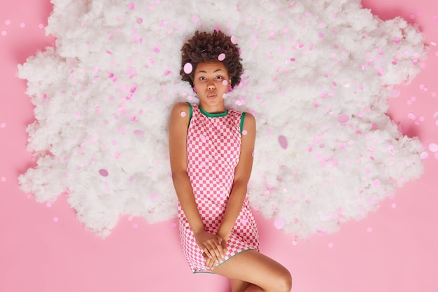 Romantic curly haired young woman dressed in checkered dress poses on white cloud