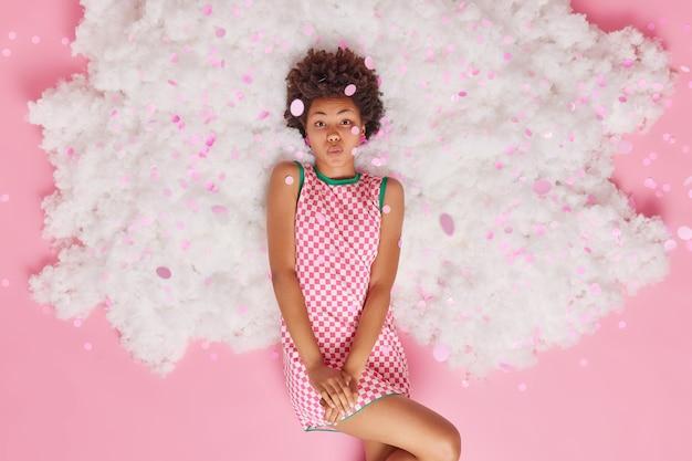白い雲の上の市松模様のドレスのポーズに身を包んだロマンチックな巻き毛の若い女性