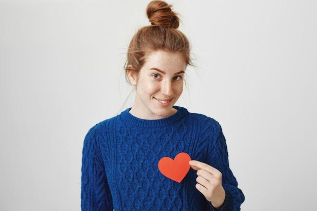 Романтическая милая рыжая девушка держит знак сердца
