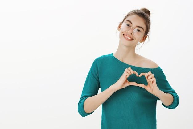 Romantica e carina giovane donna che mostra il gesto del cuore, amore o qualcosa di simile