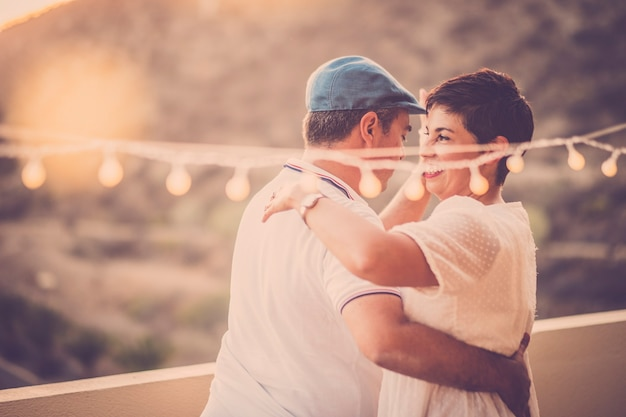 Romantic dance with middle age adult couple dancing together outdoor with nice light