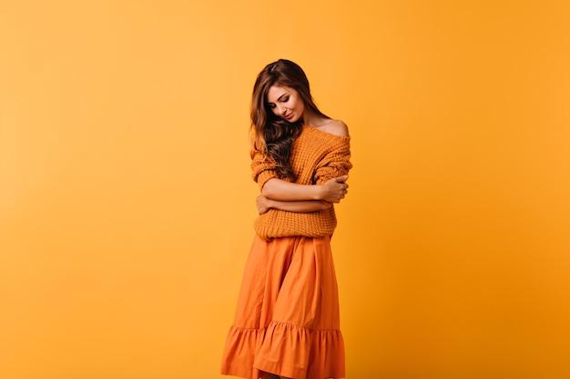 Романтичная темноволосая дама в уютном свитере позирует на желтом. добродушная женская модель в оранжевой юбке смотрит вниз.