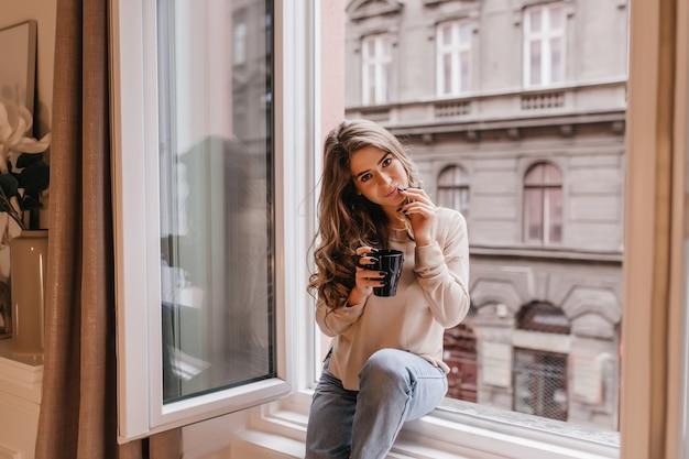 Романтичная темноволосая женщина проводит время дома и пьет латте на подоконнике