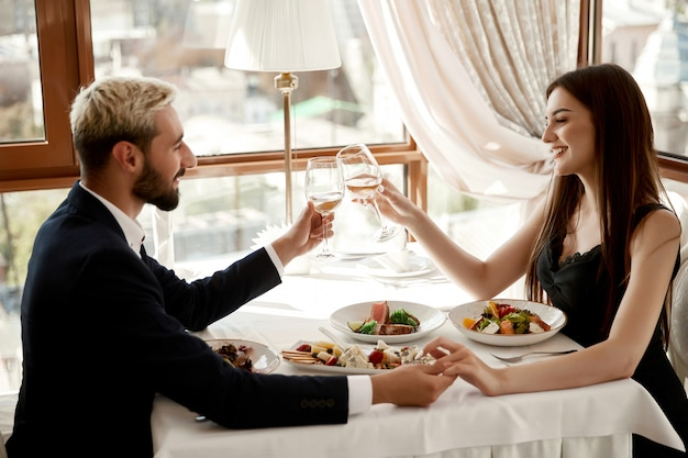 Romantic date of a handsome young man and attractive brunette woman at the restaurant
