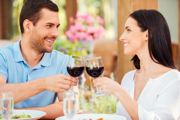Романтическое свидание в ресторане. счастливая молодая влюбленная пара, поджаривающая тост с красным вином и улыбаясь во время отдыха в ресторане на открытом воздухе вместе