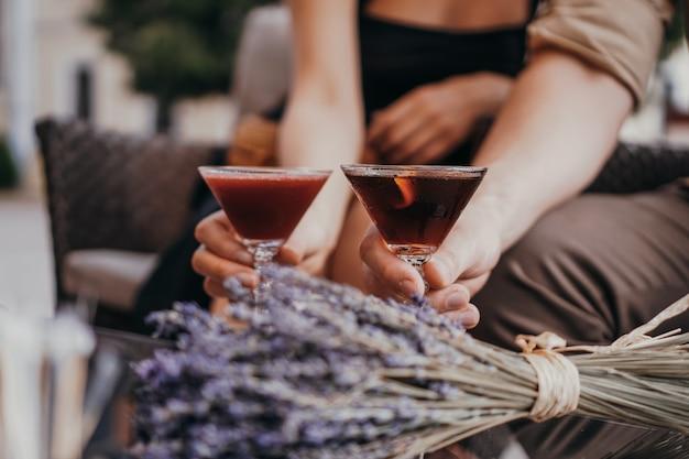 ロマンチックなデート。テーブルで手をつないでいる恋人たち。表面のカクテル。愛の概念。表面に乾燥したラベンダーの房