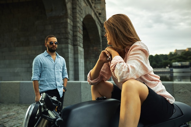 Romantic date on motorbike. young woman sits on a motorcycle and looks at the man who comes to her