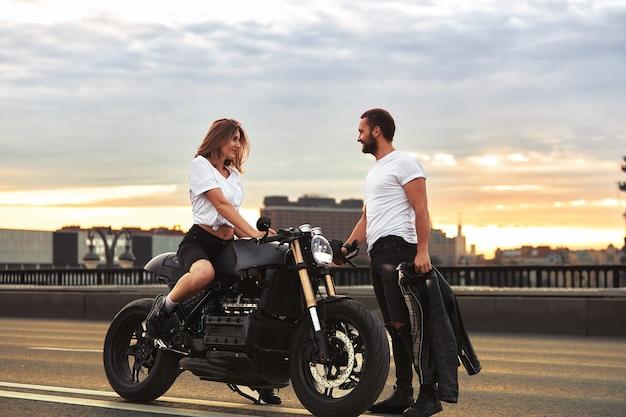 오토바이에 낭만적 인 데이트. 젊은 여성이 오토바이에 앉아 그녀에게 오는 남자를 바라 봅니다. 도시에있는 다리에 일몰과 사랑에 빠진 커플.