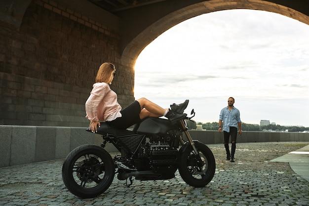 Романтическое свидание на мотоцикле. молодая женщина садится на мотоцикл и смотрит на мужчину, который к ней подходит. влюбленная пара на закате под мостом в городе.