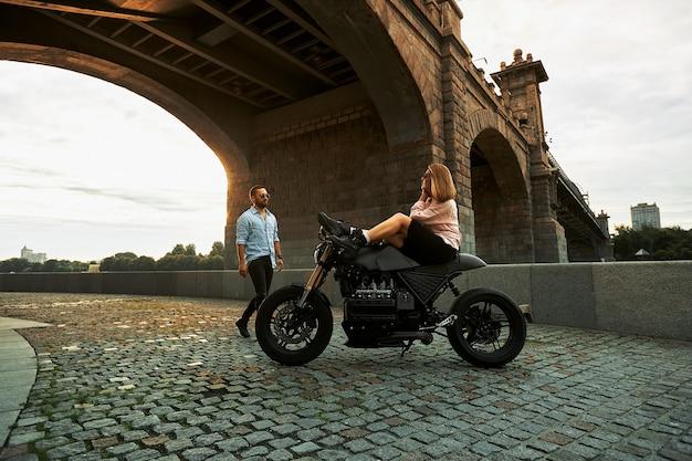 오토바이에서 낭만적인 데이트. 젊은 여자가 오토바이에 앉아 그녀에게 오는 남자를 바라본다. 도시의 다리 아래 일몰과 사랑에 빠진 커플.