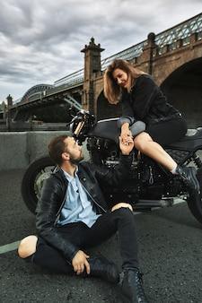 Романтическое свидание на мотоцикле. молодая женщина сидит на мотоцикле и смотрит на мужчину, который сидит на земле и держит ее за руку. влюбленная пара на закате под мостом в городе.