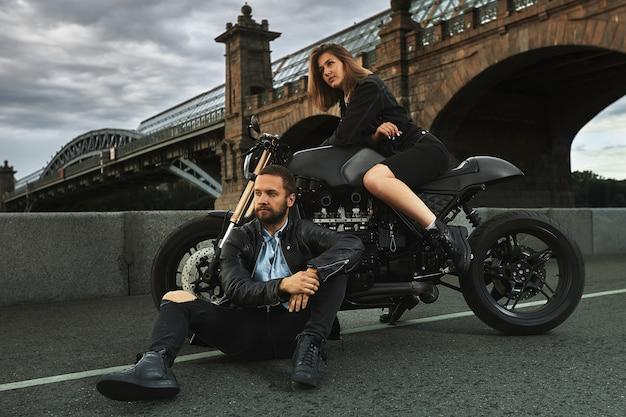 バイクのロマンチックなデート。若い女性はバイクに座って、地面に座っている男性を見ています。街の橋の下で夕日に恋するカップル。