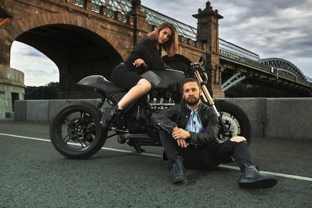 Романтическое свидание на мотоцикле. молодая женщина сидит на мотоцикле и смотрит на мужчину, который сидит на земле. влюбленная пара на закате под мостом в городе.