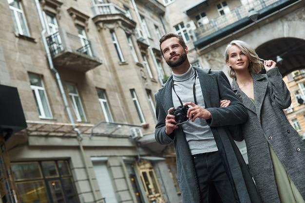 ロマンチックなデート屋外の若いカップルが街の通りを歩いてカメラの笑顔で写真を撮る