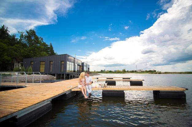ロマンチックなデートのサプライズ。若い男と木製の桟橋の女性。桟橋に座って抱擁とキス。ロマンチックなラブストーリー