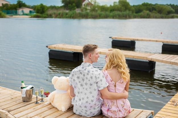 ロマンチックなデートのサプライズ。若い男と木製の桟橋の女の子。桟橋に座って抱擁とキス。ロマンチックなラブストーリー