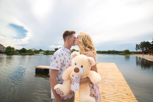 Romantic date surprise. a young guy and a girl on a pier overlooking the lake. the guy gives the girl a teddy bear.