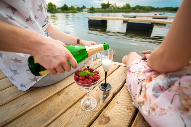 Romantic date surprise. a young guy and a girl on a wooden pier. the guy pours champagne into the glasses.