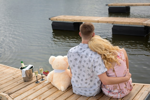 Romantic date surprise, a young guy and a girl on a wooden pier, hug and kiss while sitting on the pier, romantic love story