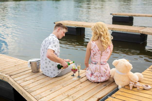 Romantic date surprise. young guy and a girl on a wooden pier.