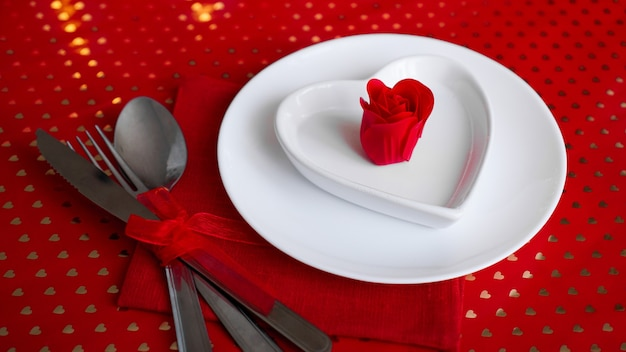 休日のテーブルのロマンチックな装飾。赤いバラとハートの形をした白いプレート。赤い背景