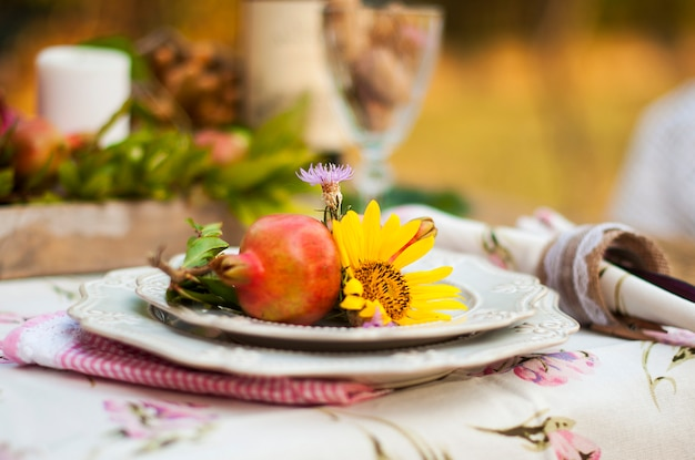 Romantic dinner in the autumn garden, table setting for a nice dinner. wine, fruit, pomegranate and flowers. picnic in the open air.