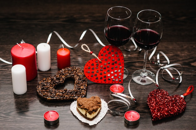 A romantic dinner, candles, concept of st. valentine's day. cake, glasses of wine. heart with coffee beans. decorated red hearts on brown wooden surface. composition love. space for text. side view