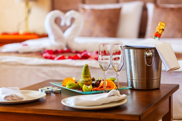 恋人のためのロマンチックなディナー:フルーツプレートのテーブル、シャンパンのグラス、金属製のバケツとキャンドルに氷を入れたシャンパン、壁にタオルとバラの花びらの白鳥で飾られたベッド