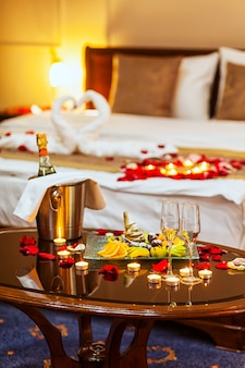 Романтический ужин для влюбленных столик с фруктовой тарелкой, бокалами шампанского, шампанского со льдом в металлическом ведре и свечами.