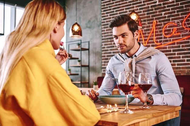 ガールフレンドと食べて話している青いシャツのロマンチックなディナーの男