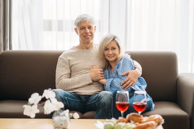 Романтический ужин взрослой влюбленной пары дома. зрелые муж и жена сидят на диване и обнимаются, счастливая семья