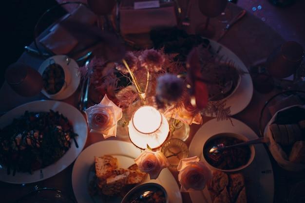 레스토랑의 가난한 촛불에서 낭만적인 저녁 식사 핑크 장식 테이블