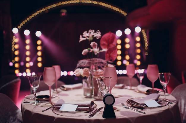 Romantic dinner pink decor table at restaurant with stage