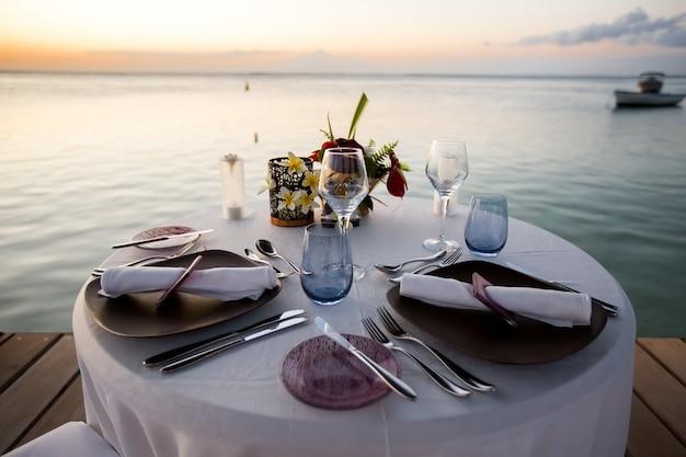 夕暮れ時のビーチでロマンチックなディナーの設定