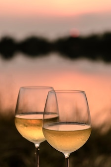 A romantic dinner in summer on a beach at sunset with two glasses of white wine