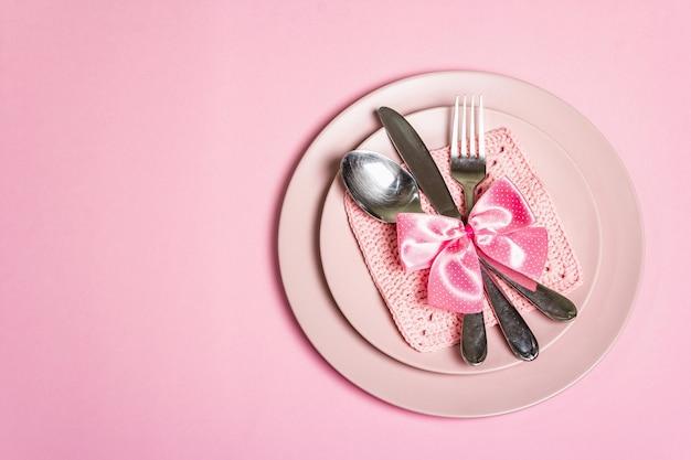 Романтический обеденный стол. концепция любви на день святого валентина или день матери, свадебные столовые приборы. минималистичный стиль, розовые тарелки, вязанная крючком салфетка, бантик в горошек, вид сверху