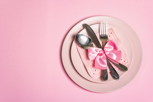 Romantic dinner table. love concept for valentine's or mother's day, wedding cutlery. minimalistic style, rose plates, crochet napkin, polka dot tied bow, top view