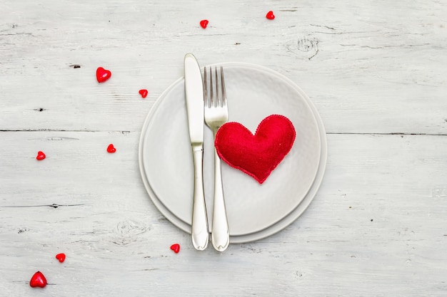 Romantic dinner table. love concept for valentine's or mother's day, wedding cutlery. soft felt heart, white vintage wooden boards background