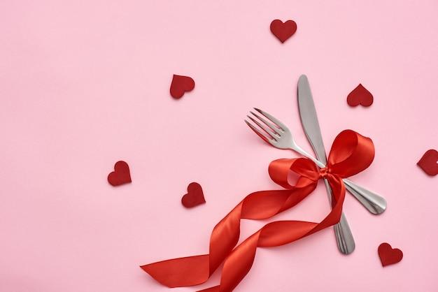 Сервировка романтического обеденного стола с красной лентой и декоративными сердечками